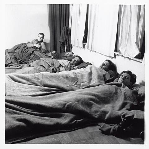 012128 - WO2 ; WOII ; Tweede Wereldoorlog. Bevrijding. Geallieerde soldaten op hun geïmproviseerde bed in huis bij een Tilburgse familie waar zij na de bevrijding tijdelijk werden ingekwartierd