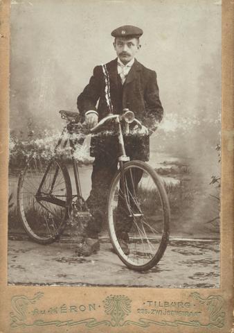 651688 - Wilhelmus van den Brekel. Toen deze foto genomen werd, was de fiets - die toen nog rijwiel genoemd werd - echt een noviteit. De man op de foto is trots op zijn bezit, heeft 'm mee naar binnen genomen om op het Oosters tapijt in de studio 'Au Herón' van fotograaf Berssenbrugge, vereeuwigd te worden. De fotozaak bleef tot 1906 in de Zwijsenstraat gevestigd en Berssenbrugge was gespecialiseerd in het maken van levensgrote portretten. Over Wilhelmus van den Brekel is het volgende bekend: hij werd geboren in Goirle op 18 augustus 1872 (dus is op de foto rond de 30 jaar oud). Zijn vader was thuiswever  en Van den Brekel trad in zijn voetsporen. Hij werkte in een linnen- en later wollenstoffenweverij in Tilburg. Hij trouwde op 28 september 1904 met Theresia van Weereld, weduwe van A.J. van de Pol. In oktober 1910 verhuisde het echtpaar naar Goirle om in februari 1918 naar Viersen in Duitsland te vertrekken. Drie jaar later keerde het gezin weer terug.