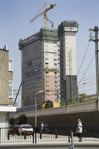 TLB023000873_002 - Zicht op het in aanbouw zijnde Interpolis gebouw, gezien vanaf het NS-Plein, met op de voorgrond de Zuid-Oosterstraat en de spoorbaan met passerende trein.