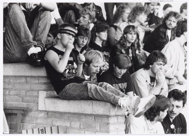 043418 - Op 4 sept.1988 vond in het Willem II stadion van Tilburg een muziekevenement plaats getiteld 'Monsters of Rock', dat tegen de verwachting in goed verliep, dankzij verlaging van het alcoholpercentage in bier naar 2%. Met haarband de 8-jarige Timothy Provily, de 8-jarige zoon van Jan Provily die naast hem zit. Vader en zoon waren vanuit Den Helder naar Tilburg afgereisd.