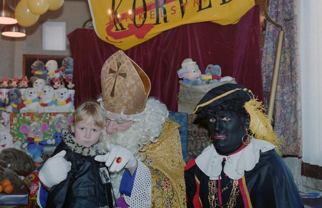 1237_001_003_012 - Feest. Korvel Winkelstraat. Sint Nicolaasviering. Een kind poseert met Sinterklaas en Zwarte Piet tijdens een Sinterklaasfeest georganiseerd door winkeliersvereniging Korvel Vooruit op 27 november 1999.