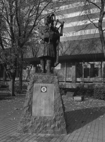 TLB023000123_001 - Oorlogsmonument voor de 15th Scottish Division is een bronzen beeld van de Schotse doedelzakspeler (Bagpiper) ter herinnering aan de geallieerde militairen en de bevrijding in oktober 1944. Het standbeeld is een ontwerp van Frans Broers en onthuld op 27 oktober 1989. Op het voetstuk is een afbeelding van een heraldische leeuw aangebracht. In 2017 is het monument verplaatst naar het Vrijheidspark.