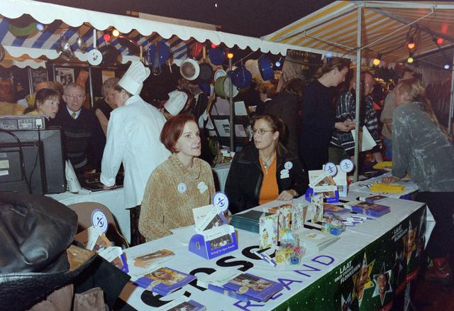 """1237_001_037_015 - Vrijwilligerswerk. Een feestelijke bijeenkomst van Stichting Contour in Theater De Vorst (tegenwoordig theater de Nieuwe Vorst) in december 1997. De stand van """"Mensen in Nood"""" op de informatiemarkt."""