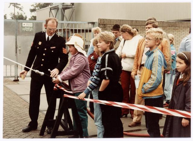 039466 - Volt, Noord. Hulpafdelingen, Brandweer. Demonstratie, tijdens de open dag, van de Volt op 15 september 1984 ( 75 jaar Volt). Brandweerman Toon van Swam laat de jeugd meedoen.