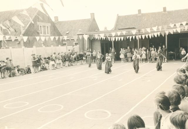 651626 - Meisjesschool Vincentius. Tilburg. Gehuld in jutte zakken proberen de zesde klassers onder het toeziend oog van de meisjes uit de lagere klassen, de overkant te bereiken.