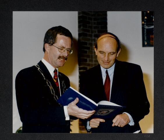 """91244 - Made en Drimmelen. Overhandiging van het boek 'Zo'n echte ark van Noë"""" bij de officiële opening van het Sociaal Cultureel Centrum """"De Mayboom"""" in Made door (links) burgemeester Jan Elzinga (1990-2004) aan (rechts) Frank J.M. Houben, commissaris van de koningin in Noord-Brabant (22.4.1987 - 27.9.2003). Het boek, geschreven door A.L. van Geertruij, schets de komst van de Liefdezusters (1853 - 1964) in Made tot de opening van het bovenvermelde centrum."""