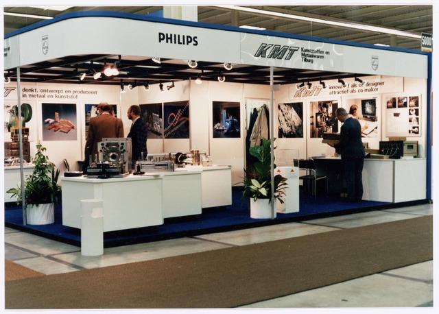038961 - Volt Noord. Tijdens een grote herstructurering bij Volt die in 1987-1988 haar beslag kreeg werd de oude  afd. kunststof en metalen onderdelen ( de oude Metaalwaren) omgezet in een geïntegreerd bedrijf. D.w.z. met eigen gereedschapontwikkeling en matrijzen- en stempelmakerij. Doel was 50% van de omzet buiten Philips te maken.  De nieuwe afdeling kreeg de naam K.M.T., Kunststoffen en Metaalwaren Tilburg. In 1991 kreeg het bedrijf een eigen directie onder de vlag van Philips.  In 1988 richtte men een stand in (foto) in de jaarbeurshallen te Utrecht waar de VAT 88 Technishow werd gehouden. V.l.n.r. N.N., Jan Roozen en van Doleweerd, beiden van K.M.T.  In 2000 werd het bedrijf door Philips verkocht aan Key Tec. In 2001 werd de productie verplaatst naar een Key Tec vestiging in Eindhoven zodat er sindsdien niets meer van de oude Volt in bedrijf is in Tilburg. Dit afgezien van een aantal uitstekende gereedschapmakerijen en de Stichting Vakopleiding Metaal die hun wortels bij Volt hadden.