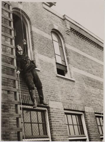 103692 - Brandweer. Brandweer oefening. Hier laat een brandweerman zich zakken met een touw.