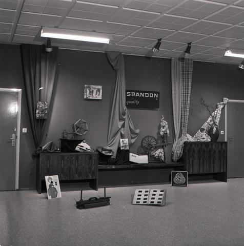 654991 - Een toonzaal van de textielfirma van André van Spaendonck & Zn.  Deze wollenstoffenfabriek werd in 1898 opgericht door Andreas van Spaendonck, eerder medefirmant van Gebroeders van Spaendonck. Het bedrijf startte aan de Koestraat en breidde zich daar in de loop der tijd aanzienlijk uit. Ook ontstond er vlakbij een fabriekscomplex aan de Enschotsestraat. In 1960 werd nog een fabriekscomplex gebouwd op industrieterrein Kraaiven. Tien jaar later moest het bedrijf, dat ook bekend was onder de naam Spandon, mede wegens de buitenlandse concurrentie de deuren sluiten. Er werkten toen nog 630 personen.