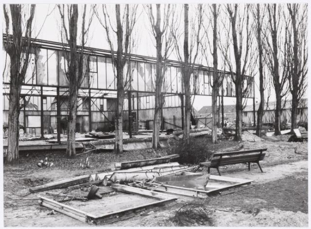 039173 - Volt. Zuid. Nieuwbouw, Gebouwen. De sloop van het stalen afval- en papiermagazijn t.b.v. nieuwbouw hal Z en het hoofdkantoor AH in 1959. De ruimte vóór de populieren was het Voltpark.