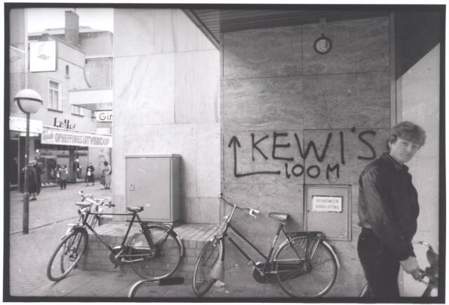 021939 - Graffiti op een muur bij de ingang van Vroom & Dreesmann in de Heuvelstraat