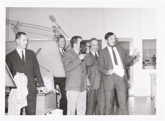 039468 - Volt. Noord? Technische Afdelingen, Tekenkamer. Simon Groot links en Frans Rijth 2e van links kijken toe bij de opnames door een fototeam van Philips Eindhoven omstreeks 1965.