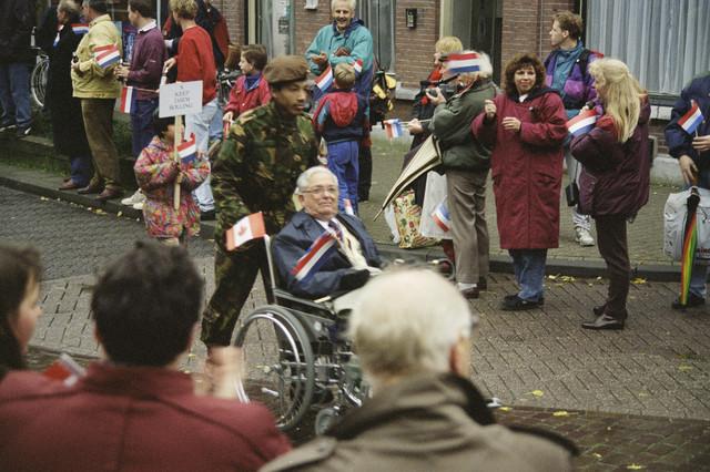 TLB023000796_005 - Een veteraan in een rolstoel wordt begeleid door een Nederlandse militair.