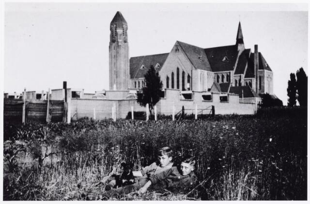 012035 - Achterzijde Kerk BroekhovenII in 1941. In het koolzaadveld links Jan Klomp en rechts Sjel Willemse.