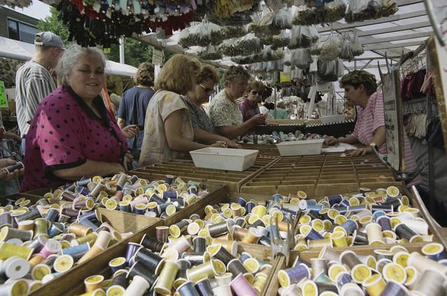 TLB023000510_001 - Bezoekers bij een fourniturenkraam op de woensdagse markt. Deze markt is bekend vanwege de vele stof- en fournituren verkopers, naast kleding en de gebruikelijke aardappel, groenten en fruit, vis en bloemen aanbieders.