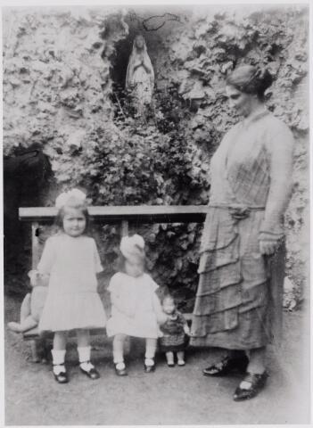 045890 - Lourdesgrot in de tuin van textielfabrikant Jan van Besouw aan de Tilburgseweg in Goirle. Rechts diens tweede vrouw, Johanna Maria Vromans, geboren te Goirle op 31 mei 1892 en overleden te Schaijk op 22 november 1978. Links dochter Ans van Besouw, geboren te Goirle op 3 november 1921, en in het midden dochter Trees van Besouw, geboren te Goirle op 11 november 1923.