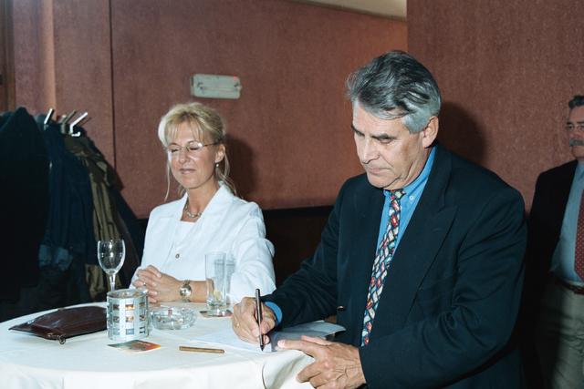 1237_002_202_007 - Gasten tijdens een feestelijke bijeenkomst voor Verkeersschool Tilburg in april 2000. De rijschool ontvangt het certificaat van goedkeuring. Onder andere burgemeester Johan Stekelenburg is aanwezig, hij maakt nog een aantekening in zijn papieren.