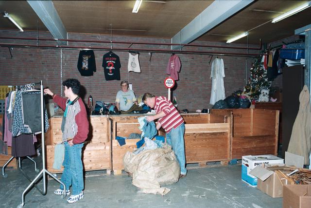 1237_010_756_020 - Winkels. Kringloop. Het interieur van kringloopbedrijf La Poubelle aan de Hoevenseweg. Ingeleverde kleding wordt gesorteerd in bakken om later verkocht te worden.