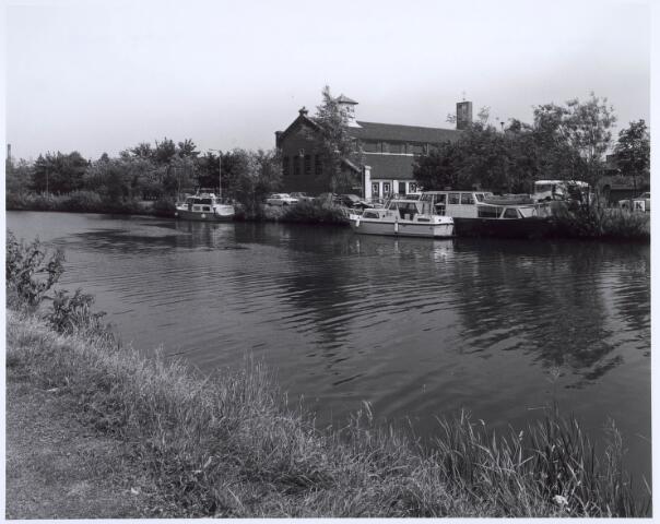020623 - Plezierboten in het Wilhelminakanaal aan de Havendijk. Op de achtergrond de voormalige noodkerk van de parochie Koningshoeven, nu supermarkt Jumbo