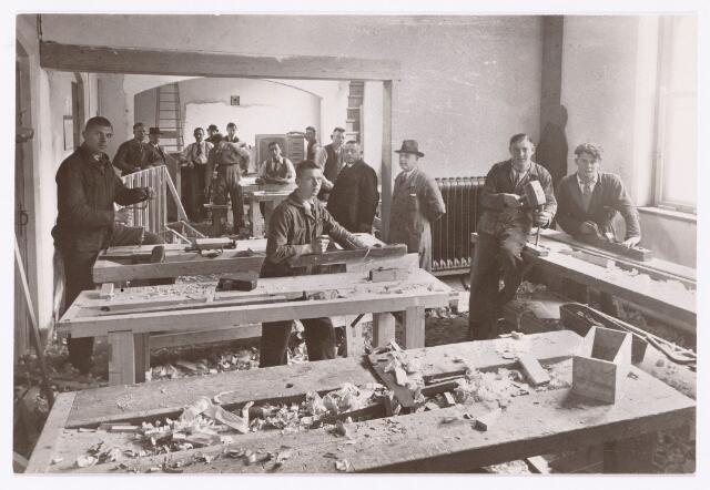 051856 - Lager en Middelbaar Voortgezet Onderwijs. Rijkswerkplaats voor jeugdige Werklozen. Werkeloze timmerlieden bezig in het oude St. Rochus gesticht.