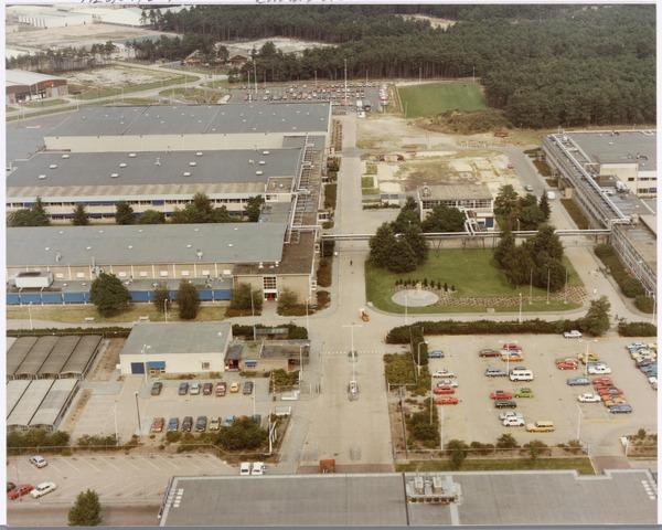 039157 - Volt, Algemeen, Luchtfoto. Voltterrein, fabricagecomplex Noord in 1980 met op de voorgrond links de personeelswinkel en de bewakingsloge. Midden  in cirkel de Voltvonk welke in november 2002 opnieuw onthuld is op de locatie Transvaalplein, door burgemeester J. Stekelenburg (1941-2003). Van links voor naar achteren achtereenvolgens de hallen  NA, NB en NO. Het gebouw in het midden achter de cirkel is het ketelhuis NE.   Uiterst rechts de gebouwen ND en NL