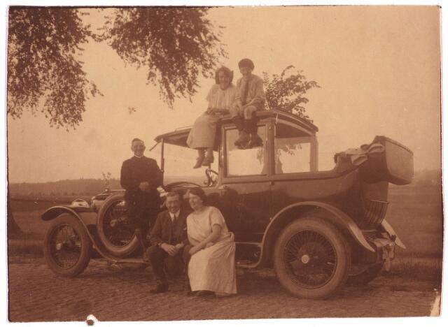 003769 - Links de chauffeur Piet van Esch, op de treeplank van de auto Minerva. Jozef Brands (1877-1959) en Marie Brands-Van Vlijmen (1884-1969) met op het autodak hun kinderen Cor en Ben.