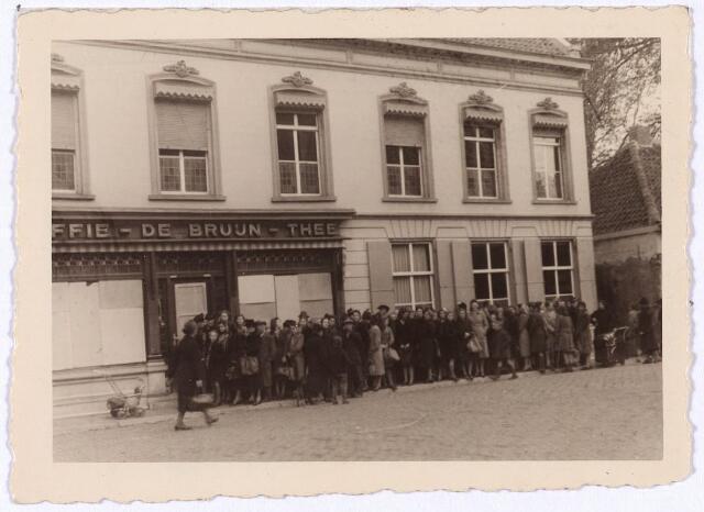 013963 - Tweede Wereldoorlog. Distributie. Een lange rij wachtenden voor de kruidenierszaak van Emile de Bruijn in de Monumentstraat op 27 oktober 1944