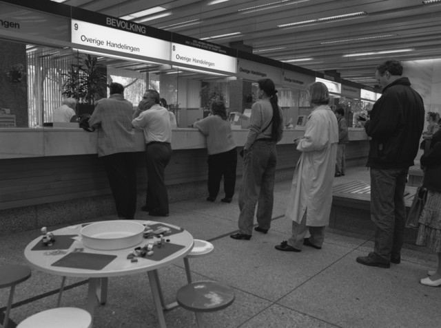 """TLB023000190_003 - Bureau Bevolking in Stadskantoor 1. Aan de diverse balies staan mensen in de rij voor aanvragen en verlenging van paspoorten, rijbewijzen, uitreksel uit de burgerlijke stand etc. Foto gemaakt in kader van """"brochure persoonsregistratie"""""""