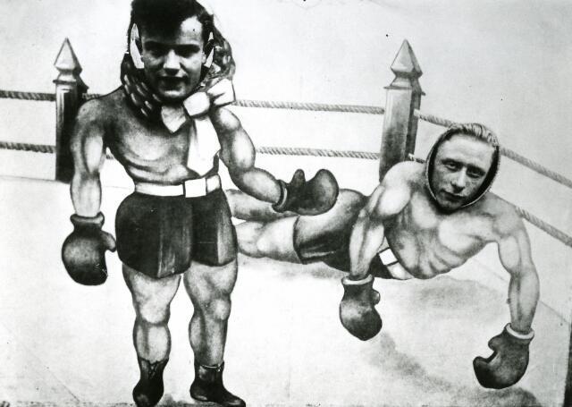 065966 - Kermis. Deze foto is gemaakt op de Heuvel. Twee mannen steken hun hoofd door een fotopaneel en doen zich voor als twee boksers.