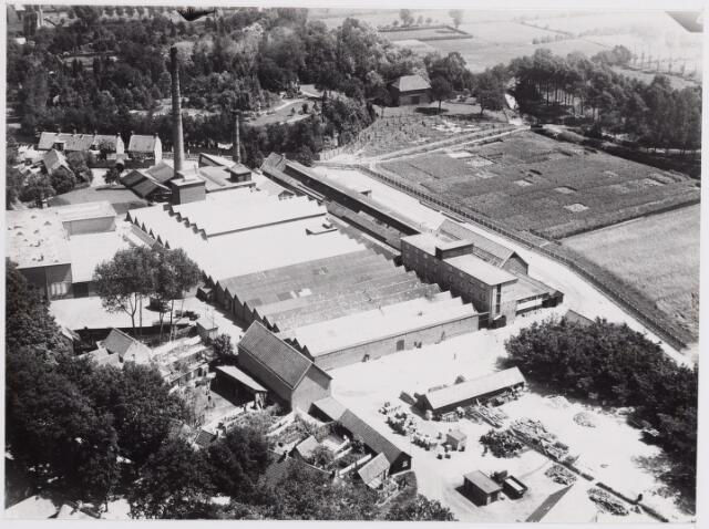 045783 - Luchtfoto van de textielfabriek van de N.V. H. van Puijenbroek. Onderaan links de Bergstraat. Bovenaan, achter de fabrieksschoorstenen, de Watermolenstraat. De voormalige watermolen, dan in gebruik als magazijn, zien we bovenaan in het midden van de foto. Links van de molen de tuin van huize Anna aan de Bergstraat.