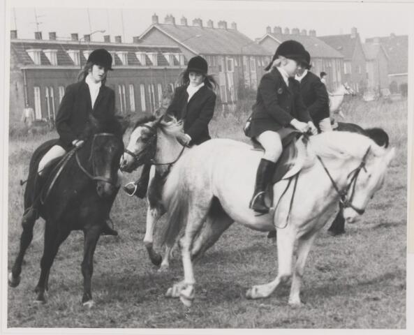 082073 - Paardensport. Ponyruiters van de Kleine Heraut uit Rijen. Dressuur viertal. Links de oude reeds gesloopte arbeiderswoningen van lederfabriek Noord-Brabant.