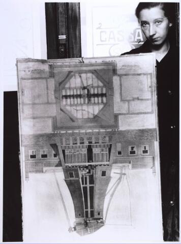 023928 - Een medewerkster van een tentoonstelling toont de tekening van de voormalige windvolmolen op Koningshoeven eind augustus 1937