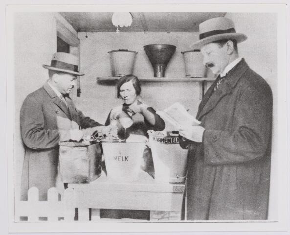 041990 - Keuringsdienst van Waren. Twee inspecteurs van de Keuringsdienst van Waren nemen een melkmonster in een speciaal hiervoor ingericht lokaal. Overeenkomstig het Melkbesluit van 1929 werd melk streng gecontroleerd omdat het een bedreiging vormde voor de volksgezondheid.