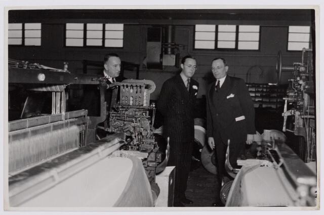 037709 - Textielindustrie. Prins Bernhard krijgt uitleg over de werking van een weefgetouw van directeur Hein Enneking sr. tijdens zijn bezoek aan de fabriek  op 13 november 1950