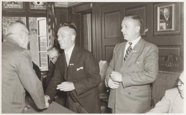 047350 - Gijs Tra (links) feliciteert Jo van Gestel met de nieuwe burgemeester. Rechts van Van Gestel A. van Iersel en Eli Peijnenborg. Tegen de wand een foto van wethouder H. Vekemans.
