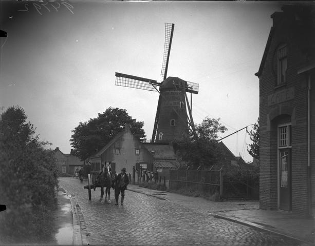 """652127-bew - Straatbeeld. Molen met (reclame-) opschriften """"...van Dijk Bierens ... fabriek"""" en """"...van Oers electriciteit"""" .  Links op de foto ingang Café .... op de straat man met paard en wagen en een fietser"""