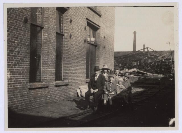 022701 - Textiel. Jos Brands met zijn kinderen voor de restanten van zijn weverij aan de Hoogvensestraat na een brand. Op de achtergrond de schoorsteen van Beka