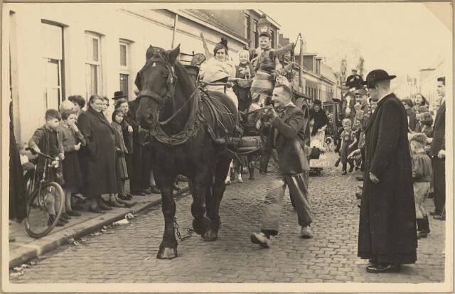 604061 - Folkloristische optocht ter ere van de bevrijding van Tilburg (27 oktober 1944);  Bewoners van de Koningswei  verbeeldden een 'Boeren overtrek'. Een folkloristisch gebruik waarbij de bezittingen van een boerengezin door de nieuwe buren op een boerenkar werden verhuisd en werden afgeleverd op het nieuwe adres. Daarna werd er gefeest waarbij 'stevig drinken' het belangrijkste onderdeel vormde.  De pastoor en buurtbewoners kijken langs de kant van de weg toe