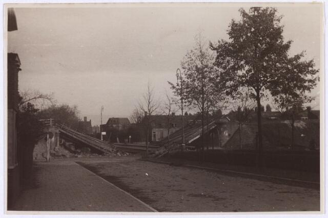 012720 - WO2 ; WOII ; Tweede Wereldoorlog. Herstel. Twee dagen na de bevrijding. Vernielde spoorbrug aan de Ringbaan-Oost, gezien in de richting van de Bosscheweg. Rechtsachter de Sacramentskerk.