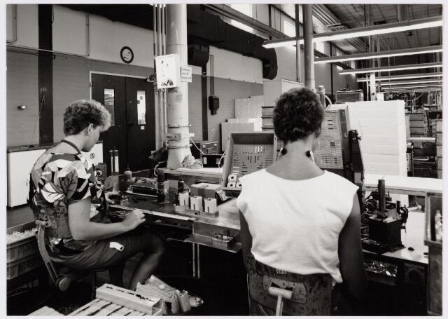 050171 - Volt, Industrie, Lijntransformatoren, LOT. Opname in hal NA ( complex Noord ) waar de produktie plaats vond van de lijntrafo, ook wel LOT genoemd.  De foto is gemaakt in augustus 1984. De dame rechts is Mw. Buster.