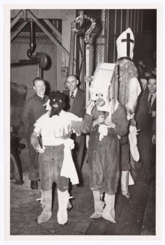 """039399 - Volt, Zuid. Ontspanning. Technische Afdeling, Gereedschapmakerij. De intocht van """"Sint Nicolaas"""" in waarschijnlijk de Gereedschapmakerij omstreeks 1955. Uiterst links Louis Melchiors en helemaal rechts Ton Klomp. De Sinterklaas is waarschijnlijk Sjaak v.d. Ben van de magazijndienst."""
