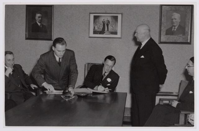 037646 - Textiel. Prins Bernhard tekent het gastenboek bij zijn bezoek aan Tilburg op 13 november 1950. Hij  bezocht de Hogere Textielschool en wollenstoffenfabriek H. F. C. Enneking en sprak ondermeer met vertegenwoordigers van de Kamer van Koophandel en de Katholieke Economische Hogeschool
