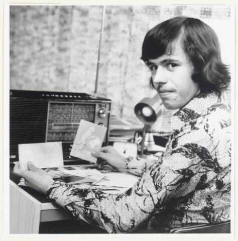 90586 - Made. André van der Velden -  radioamateur op de korte golf. Hij ontvangt kaarten van andere radioamateurs over de hele wereld, afhankelijk van het bereik van de zender. Deze kaarten, de z.g. QLS kaarten, werden verstuurd als bevestiging van de ontvangst van het radiostation. Speciaal door zendamateurs, die vaak hun eigen kaarten hadden.