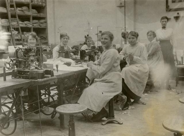 652793 - Firma Gelen Maessen. Confectie atelier van de fa. Gelen Maessen. De vrouwen droegen een stofjas ter bescherming van hun eigen kleding.  Er werd gewerkt op trapnaaimachines.