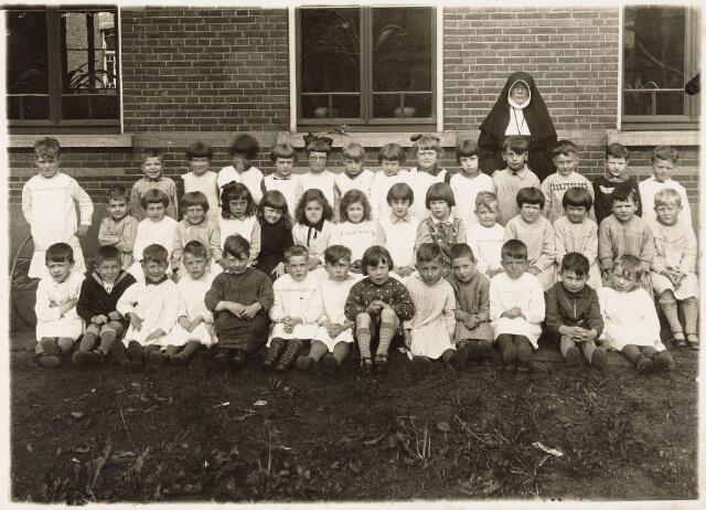 """051032 - Basisonderwijs.  Klassenfoto kleuterschool. De Heuvelse bewaarschool werd op 1 juli 1906 pal naast de Mariaschool opgericht en gebouwd . Deze bewaarschool werd gesticht door de zusters van Liefde in 1906. Het gebouw dateert van 1912. Op de foto zuster Quirina van den Berg,  die van 1906 tot 1942 les gaf op de school als """"bewaaronderwijzeres"""". De zusters van Liefde hebben tot 1964 onderwijs op deze school gegeven. Thans heet de school het Heuvels Kleuterhofke."""