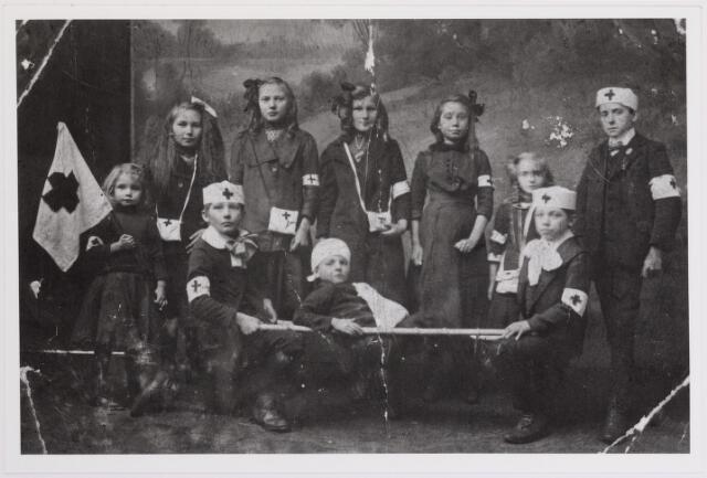042335 - Groepje kinderen uit de parochie Korvel vormen een Rode Kruisgroepje. Op de achtergrond, van links naar rechts, A. Zandbergen, J. van Sprang, M. van Sprang, B. Broers, C. Zandbergen, F. Korthout en K. Zandbergen. Voorste rij, van links naar rechts, Fr. Korthout, J. Maas en J. Broers