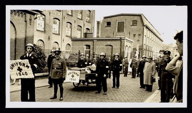 1696106 - Het Nederlandse Rode Kruis afdeling Tilburg. De colonne van het Rode Kruis Korps Tilburg tijdens deelname aan het Wolcorso (van de Wolstad Tilburg) op 31 oktober 1954. Leden van het Rode Kruis stellen zich op voor het gebouw van het Rode Kruis in de Tuinstraat. Ze presenteren uniformen door de jaren hee. In dit gebouw zat oorspronkelijk de fabriek van de Gebroeders van Spaendonck gevestigd. Het pand werd in 1929 door Fr. v.d. Berg van Aabe overgenomen. Tijdens de oorlogsjaren 1940-1945 maakte het Rode Kruis gebruik van de voormalige fabriek. In 1961 werd het gebouw aan de Tuinstraat afgebroken.