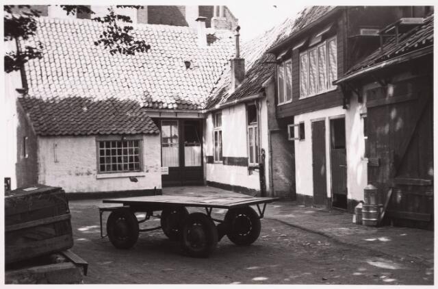 036217 - Stadhuisplein.    Monumentstraat achterzijde Café en Bodehuis Schuurmans. Op de voorgrond een platte kar.