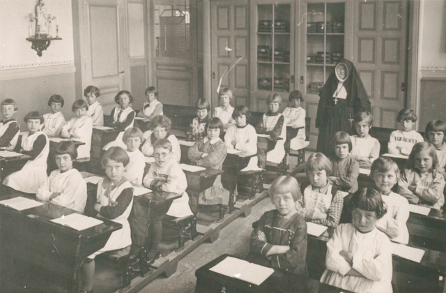 653661 - Klassenfoto, Tilburg.  Foto van de 2e klas van de R.K. Lagere Meisjesschool Korvel met Zuster Alexandrien. In de klas zaten 27 kinderen van 8 of 9 jaar. Op de meest linkse rij:  * Riekie van de Heiligenberg - Trees Melis,   * Riet Smeulders (overleden op 15 jarige     leeftijd) - Annie Hamers,  * Riet te Boekhorst (overleden) of Mien     Berkhof (overleden - Dini de Jong, * Mien van Goch. In het midden:  * Annie Naber - Trees Burgers, * Nellie Hamers - Edy van de Berg,  * Corrie van Wezenbeek -  Mien Thöhissen,  * Harriet Heerkens - Riet Gaudelius     (overleden),   * Greet van de Wijngaert - Corrie Elberse,  * Nelly Hofkens.  Rechter rij:  * Annie Hultermans - Selma Wertheim,  * Annie van Asten  - Mien Jansen,  * Riet Swolfs - Nettie van de Eijnden,  * Stan Lampen - Nellie Hamers (uit de     Korenbloemstraat),  * Betsie Klaassen.