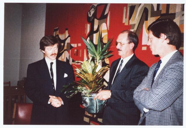 063638 - Op 24 april 1989 kwam de fractie voorzitter van de VVD in de 2e kamer, de heer Joris Voorhoeve, ter gelegenheid van het planten van een Julianaboom nabij het Mariahof, naar Berkel-Enschot: Ontvangst op het gemeentehuis aan de Eikenbosch 47; onder het toeziend oog van de heer Ligthart bied Ad Versmissen de heer Voorhoeve een bloempot aan